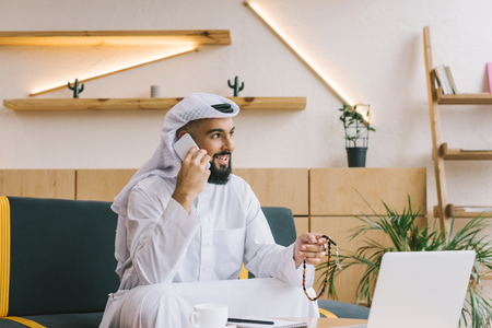 happy muslim businessman talking by phone while sitting on couch