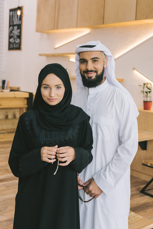 muslim couple in traditional clothing standing in modern cafe