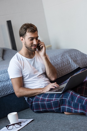 Young smiling man sitting on floor in his bedroom with laptop while talking on smartphone