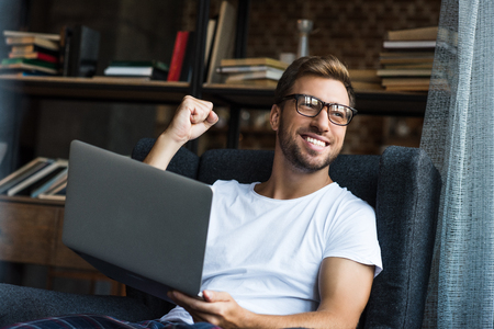Young man sitting with laptop in armchair and cheering with his fist