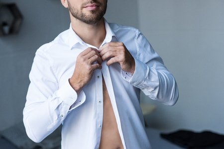 Cropped shot of young handsome man buttoning up a white shirt