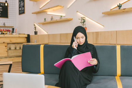 muslim woman reading magazine in cafe and talking by phone