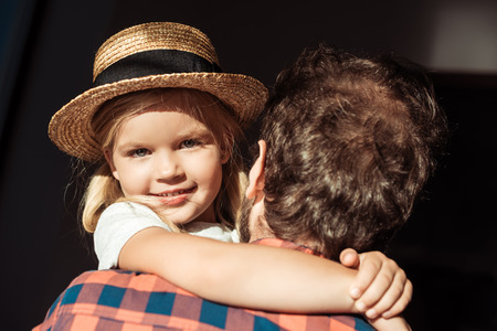 portrait of little girl in straw hat looking at camera while hugging father Banco de Imagens
