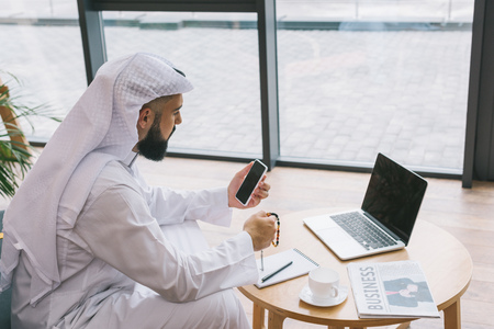 young muslim businessman using smartphone while sitting on couch with laptop on table