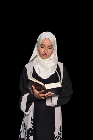 muslim woman in hijab reading quran isolated on black 免版税图像