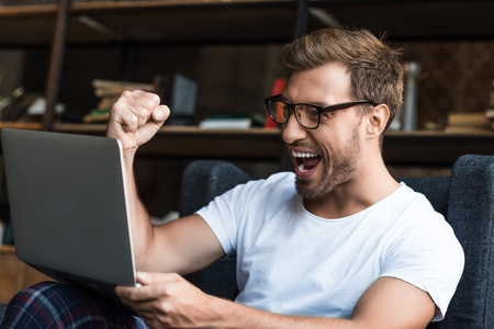 Young man sitting with laptop in armchair and cheering with his fist as he is looking at computer screen