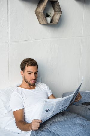 Attractive young man wearing white t-shirt, sitting in his bed and reading a business newspaper Stock Photo