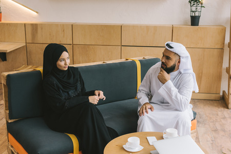 young muslim couple talking while sitting on cozy couch