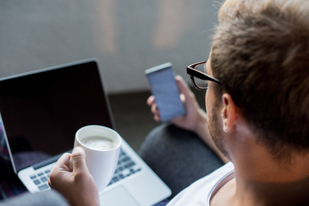 Young man using his smartphone while sitting in armchair with coffee and laptop in his lap Stock Photo