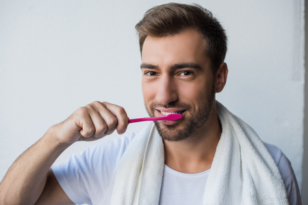 Young handsome man with towel on his shoulders brushing teeth and looking at camera