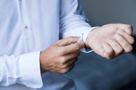 Cropped shot of a man buttoning up cuffs of his white shirt 스톡 콘텐츠 - 102296404