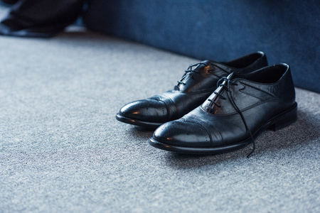 Black male leather shoes placed on carpet floor Archivio Fotografico