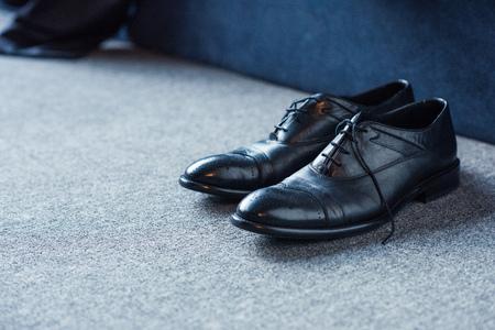 Zwarte mannelijke leerschoenen die op tapijtvloer worden geplaatst Stockfoto