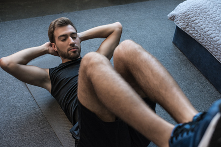 Young handsome man in sportswear doing crunch exercise on floor in his bedroom