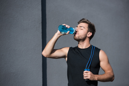 Young athletic man in tanktop holding a jumping rope and drinking water from plastic bottle Stock Photo