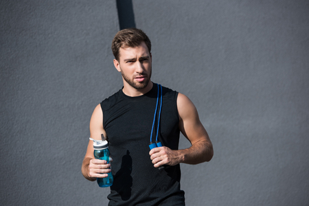 Young athletic sportsman in tanktop holding a skipping rope and bottle of water Stock Photo