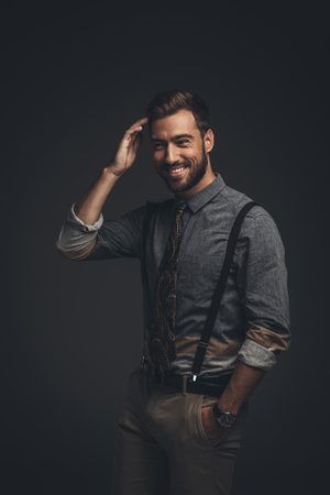 Smiling young man in suspenders posing with hand in pocket and looking at camera