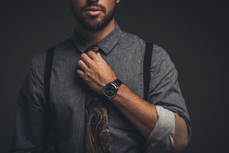Cropped shot of young bearded man in suspenders adjusting his tie