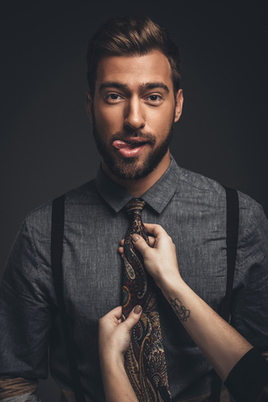 Young bearded man sticking his tongue out while female hands adjust his tie Stock Photo