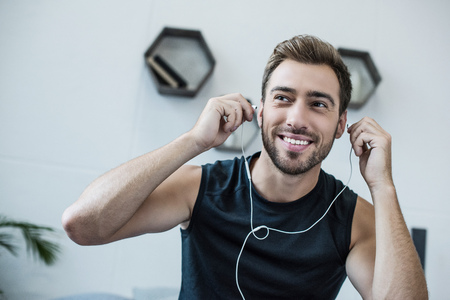 Young smiling man in tanktop putting on earbuds and looking aside Stock Photo