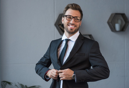 Young smiling businessman in glasses buttoning up a formal blazer Stock Photo