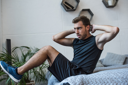 Young athletic man in sportswear doing exercises for abs on his bed