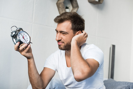Sleepy young man in white t-shirt holding an alarm clock and scratching his face Reklamní fotografie