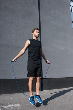 Young athletic sportsman in sportswear exercising with a jumping rope outside