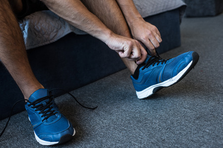 Cropped shot of man tying laces on jogging sneakers Stock Photo