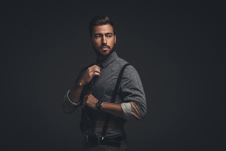 Handsome young man in suspenders adjusting his tie