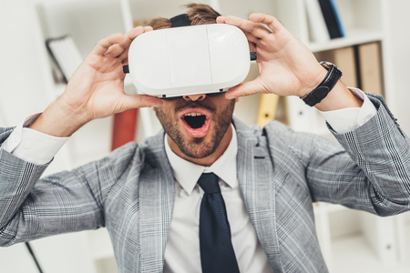 expressed young businessman in vr headset sitting in modern office