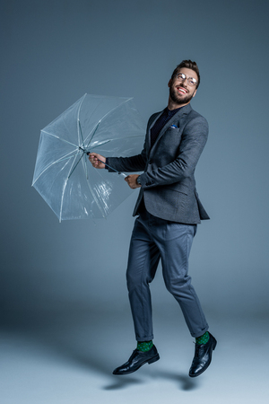 Young handsome man in suit and glasses, posing with a clear plastic umbrella