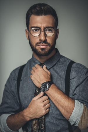 Young bearded man in glasses adjusting his tie Imagens