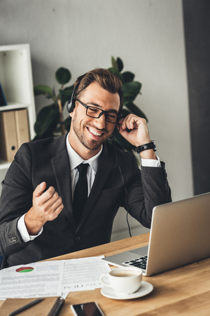 happy young call center worker in glasses making call