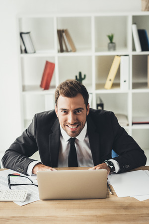 businessman with maniac face grimace working with laptop