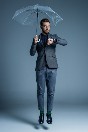 Young handsome man in suit and glasses holding an umbrella and looking at his watch