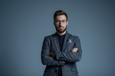 Young handsome businessman in formal suit and glasses posing with arms crossed