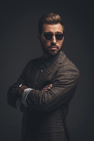 Young handsome man in suit and sunglasses standing with arms crossed, isolated on black