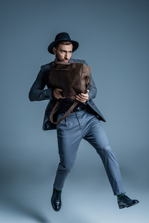 Young handsome man in suit and hat holding a leather bag like a gun