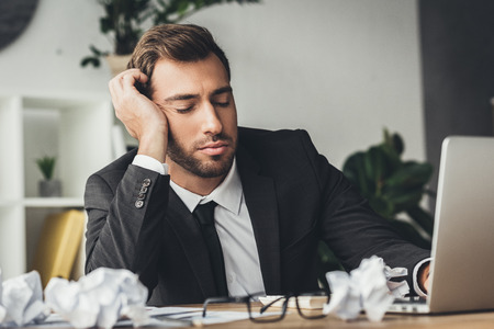 sleeping overworked businessman with crumpled papers on desk
