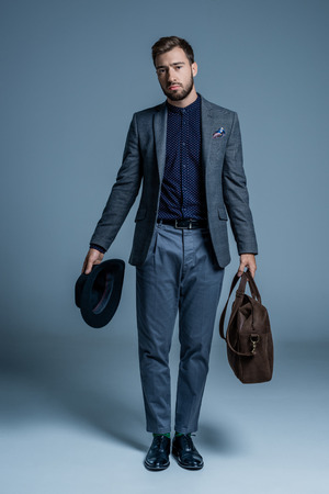 Dissatisfied young man in suit standing with hat and leather bag in his hands