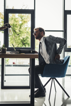 young businessman with back pain at workplace in office