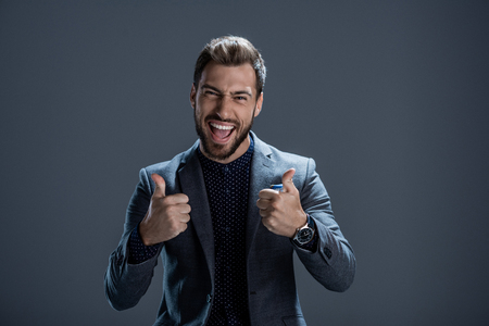 Excited young man in formal suit showing thumbs up and looking at camera