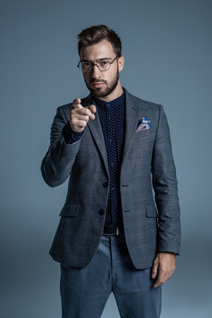 Young handsome man in formal suit and glasses pointing finger at camera