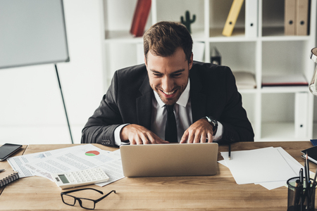 funny businessman with maniac face grimace working with laptop Stock Photo