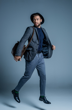 Smiling young man in suit and hat jumping up with leather bag on his shoulder