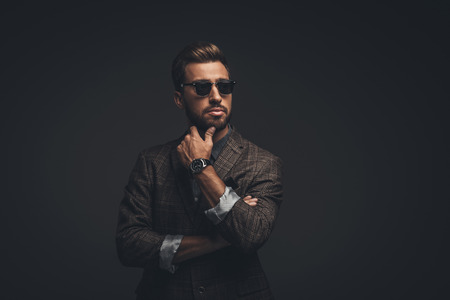 Young handsome man in suit and sunglasses posing with hand on chin, isolated on black Imagens