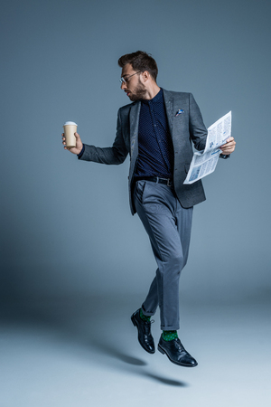 Young handsome man in suit walking with coffee cup and newspaper in his hands