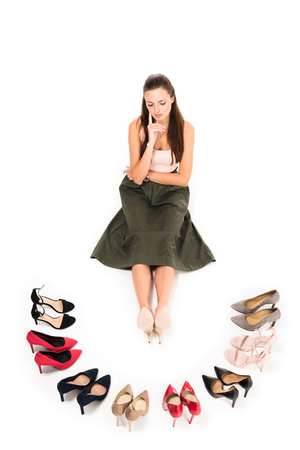 high angle view of woman sitting in front of arranged fashionable high heels isolated on white