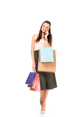 young woman with shopping bags talking on smartphone isolated on white Stock Photo